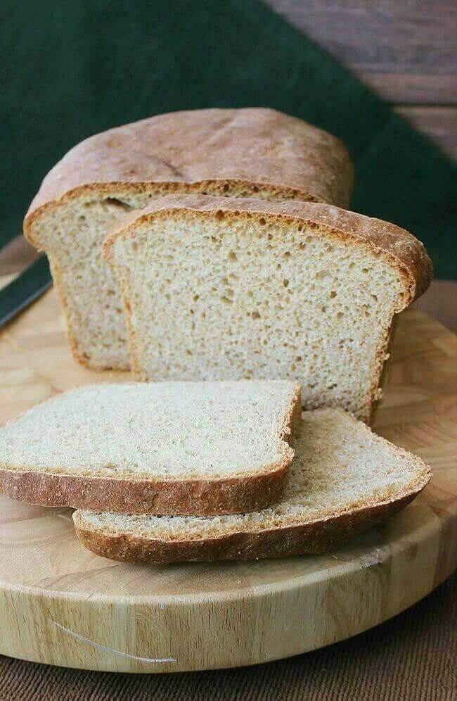 Freshly baked whole wheat batter bread is on a cutting board and it has slices cut from one end and stacked on each other.