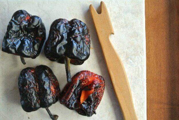 Blackened Roasted Red Bell peppers ready for stripping laying next to a wooden tool made for me as protection when pulling pans out of the hot oven.