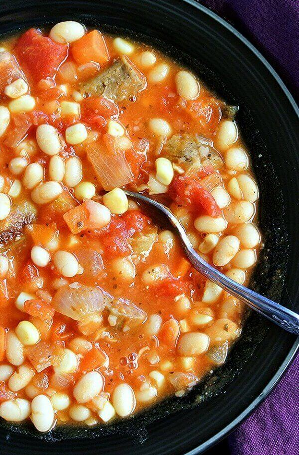 Vegan White Bean Stew up close with a spoon ready for eating.