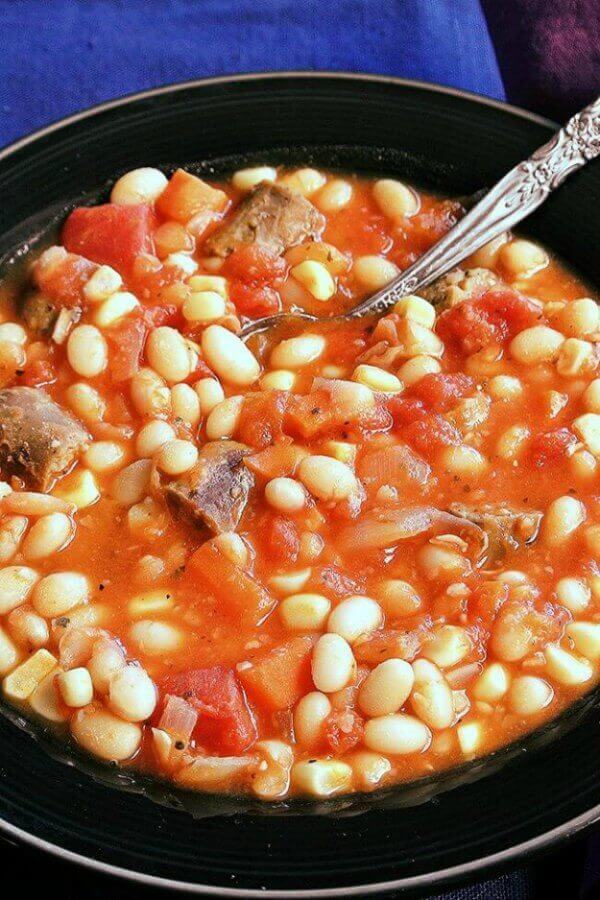 Vegan White Bean Stew is comfort food to the max. Fresh carrots, corn off the cob & to make it traditional there's also plant based sausage.