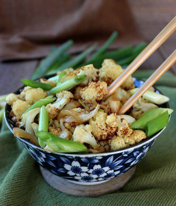 An Asian styled blue and white bowl holding cooked cauliflower with scallions and chopsticks inside of bowl too.