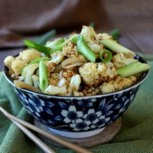 An Asian styled blue and white bowl holding cooked cauliflower garnished with scallions and chopsticks laying on the side.
