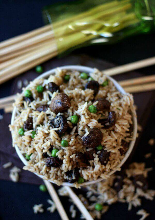 Mushrooms and rice fill a bowl with peas scattered throughout and chopsticks on the side.