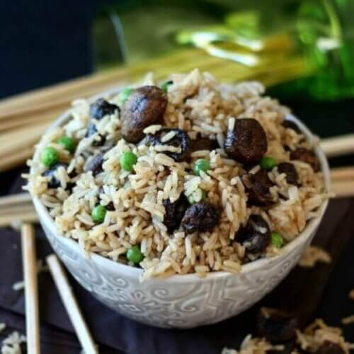 An embossed ivory bowl is tilted forward and filled with rice, mushrooms and peas with chopsticks on the side.