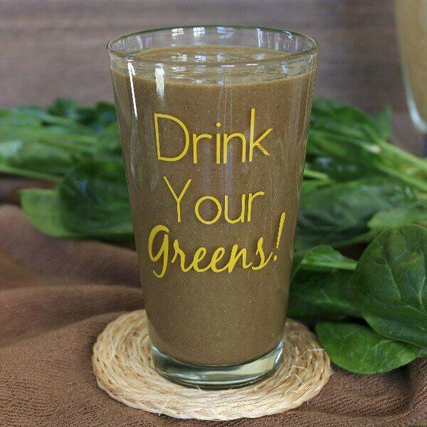 Mexican Iced Chocolate Smoothie is chocolate and is in a clear glass with Drink Your Greens printed on the front.