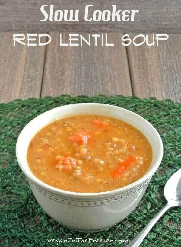 Slow Cooker Red Lentil Soup is filling a wite bowl woth rich orange soup with chinks of carrots popping up.