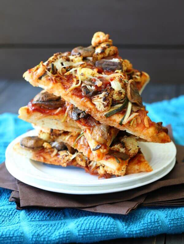 Vegan BBQ Veggie Pizza stack of pizza sliced tilted for visual of vegetables.