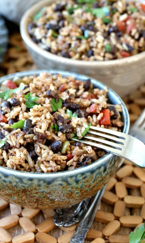 Acadian Black Beans and Rice up close view of the recipe for a better look of a perfect side dish. A fork is balancing on the full bowl of colorful contrasting black beans and brown rice.