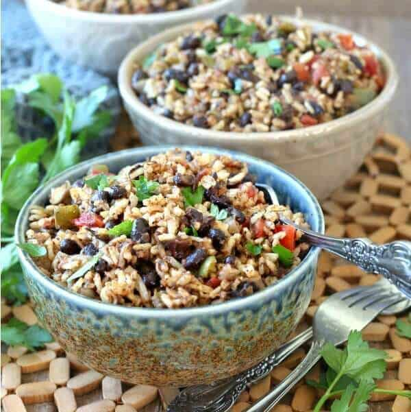 Acadian Black Beans and Rice optimized for social media shares in a square photo. Colorful black beans and rice mixed with red bells and sprinkled with green parsley.