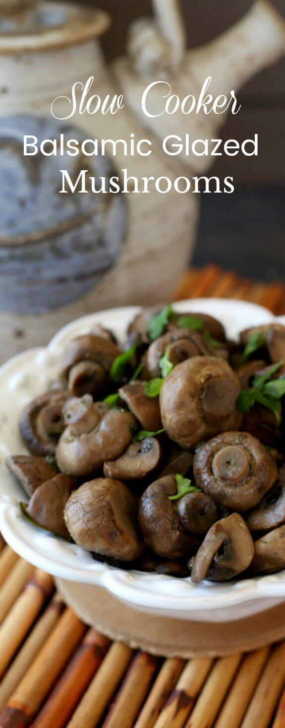 Slow Cooker Balsamic Glazed Mushrooms has the bowl full of cooked mushrooms cut in half so that there is an extreme close-up of the mushrooms that is sprinkled with fresh green parsley.