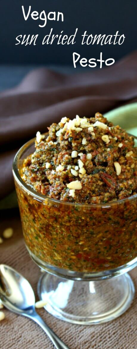 Vegan Sun Dried Tomato Pesto is piled high in a footed glass jar and titled forward.