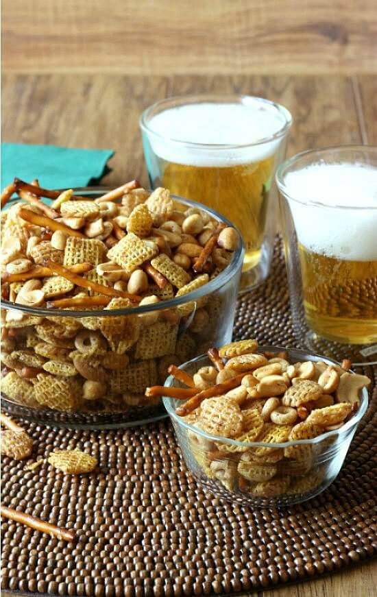 Nuts and Bolts Party Mix is piled high in two glass bowls with two foaming beers set off to the right.