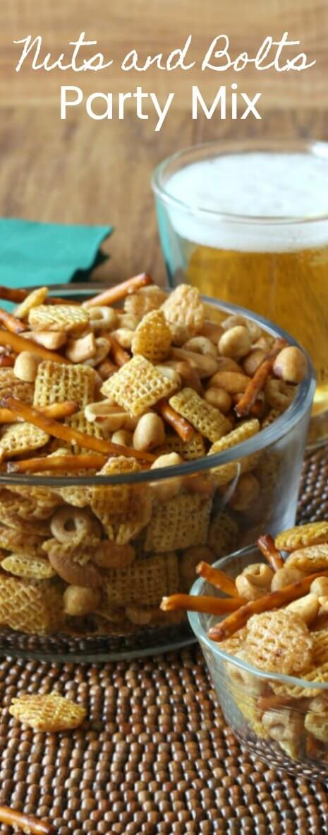 Nuts and Bolts Party Mix is piled high and close-up in two glass bowls with two foaming beers set off to the right.