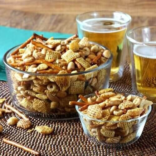 Cereal, nuts and pretzels are pled in a grear glass bowl with a smaller clear glass bowl next to it. Two beers are on the side.