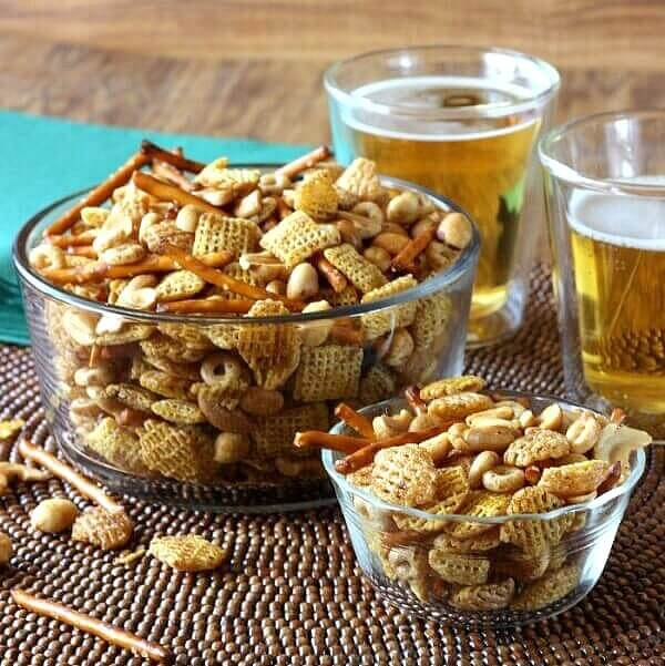 Nuts and Bolts Party Mix is piled high in a glass bowl with two foaming beers set off to the right.