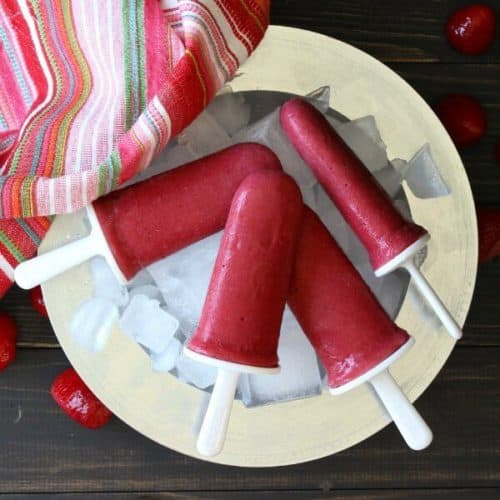 Four bright red frozen yogurt popsicles are on a bed of ice and a silver charger with a colorful striped cloth napkin on the side.