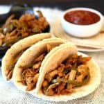 Vegan Fajitas with Meatless Chicken are sitting three to a plate with salsa on the side.