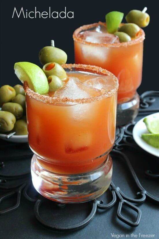 Michelada Recipe is the color of tomato red in a crystal glass. Rimmed with chli salt and green olives on a toothpick.