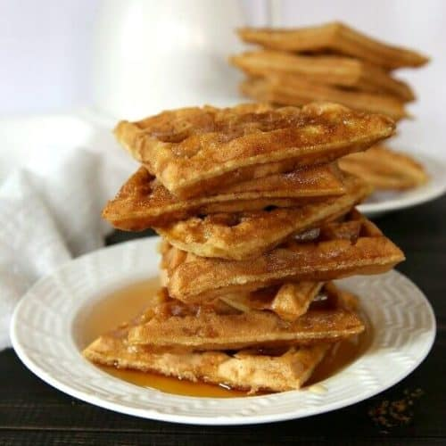 Apple wafflesare stacked seven triangles high on a white plate with syrup.