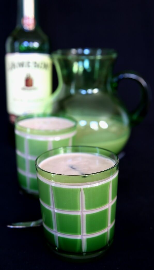 A Vegan Baileys Irish Cream Whiskey cocktail with a whiskey bottle behind.