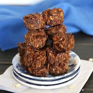 Cashew Pralines are stacked in a pyramid on a stack of three mini plates.
