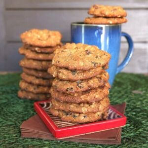 Orange Cranberry Cookies are stacked six cookies high on a red square coaster with another stack behind.