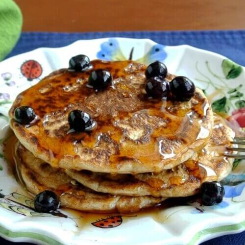 Stack of pancakes with blueberries baked inside and sprinkles on top with a fork on the side and maple syrup poured over all.