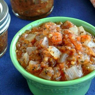 Chunk Tomato Salsa piled high in a green bowl with half pint jars stacked behind.