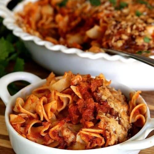 Vegan Chicken Noodle Casserole with a red marinara sauce filled in a single serving and siting in front of the big casserole.