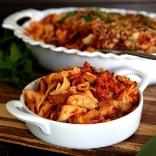 Small white bowl centered in front of the casserole and overflowing with seitan noodle casserole in a red sauce.