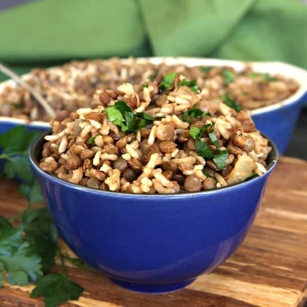 Classic Mujadara baked rice, lentils, onion and spices mounded in a cobalt blue bowl and sprinkled with parsley.