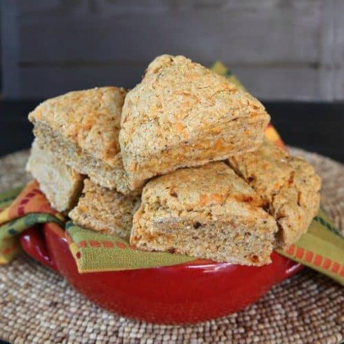 Chipotle Scones are speckled with orange dairy free cheese and red chipotle bits. Twelve triangle scones piled high in a red handles pottery bowl.