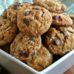 Coconut Chocolate Chip Cookies stacked to overflowing in a square ivory colored bowl.