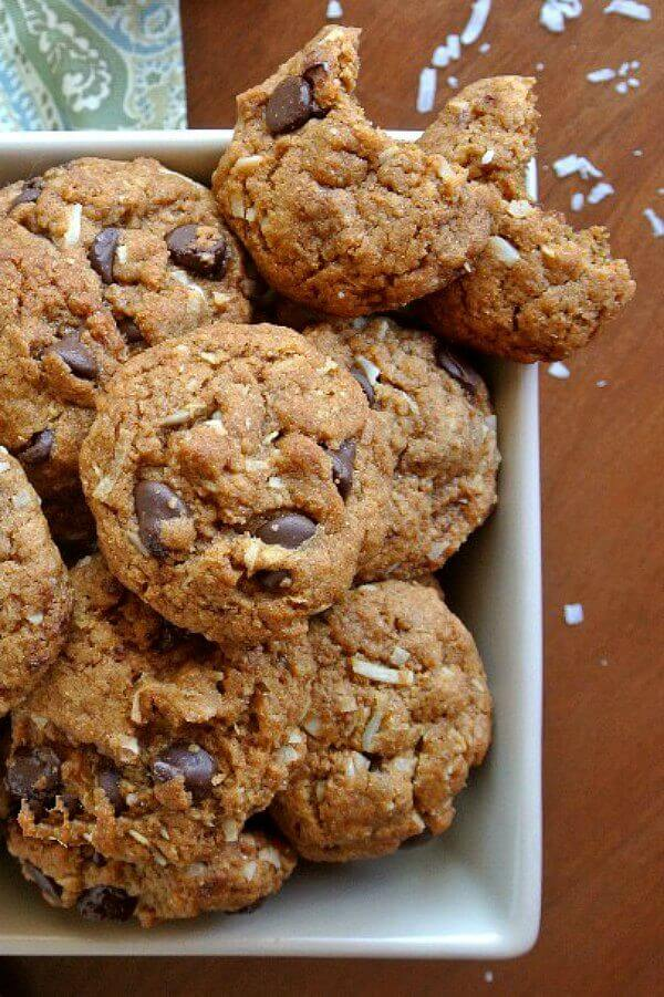 Coconut Chocolate Chip Cookies with an overhead shot of a big pile with two cookies balanced on the edge with a nice bite out if each.