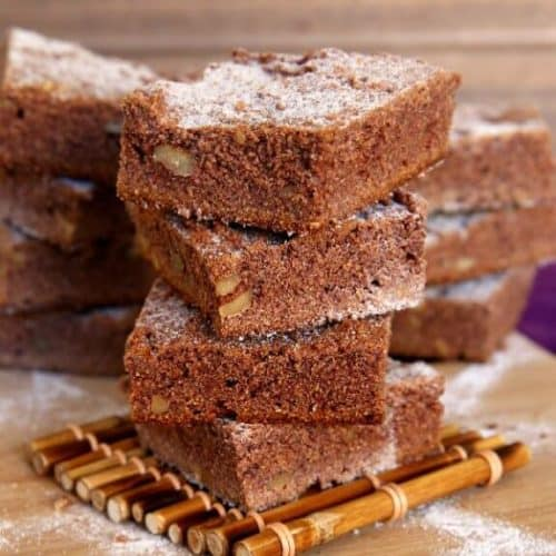 Irish Blackberry Cakes have a mild purplish tinge of blackberry jam on the inside. Stacked 4 high these square cakes are sitting on a bamboo coaster.