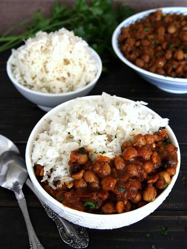Slow Cooker Chickpea Curry Recipe is loaded into a white bowl and tilted forward with chickpeas and rich red sauce.