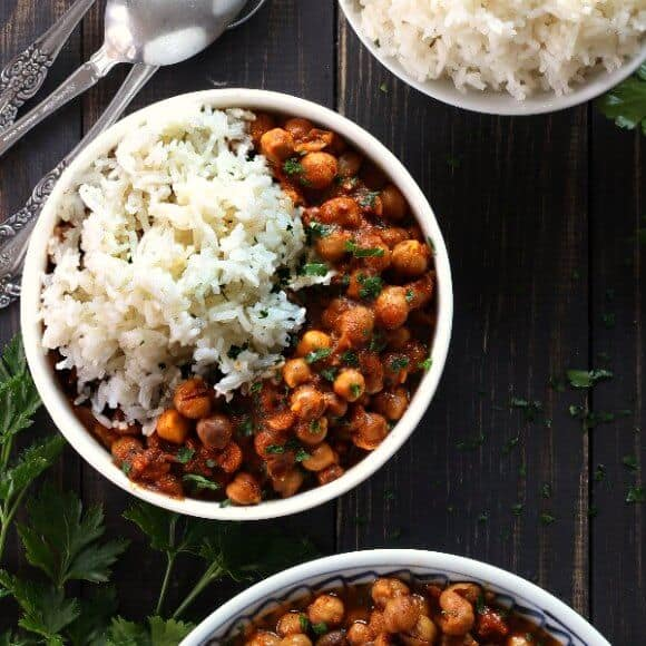 Slow Cooker Chickpea Curry Recipe with an overhead view of a bowlful of rich red sauced curry with white jasmine rice.