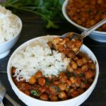 Rich red curry and chickpeas in a white bowl along side rice and a big spoonful coming your way.
