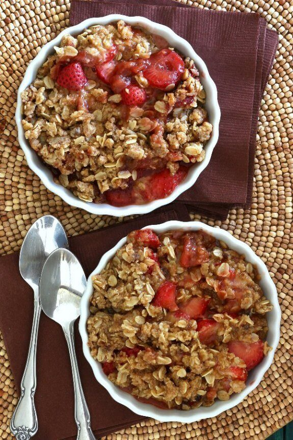 Slow Cooker Strawberry Crisp Recipe with a view from above. Two bowls are filled sliced strawberries and mixed lightly with an oat and brown sugar topping.