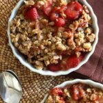 Slow Cooker Strawberry Crisp is filling a scalloped white bowl. A view from above with sweet sliced strawberries with an oat like strudel.