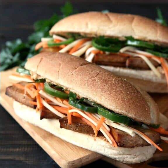 Vegan Banh Mi Sandwich is photographed as Front view of two French rolls stuffed with layers of golden tofu, orange & white julienned veggies and bright green slices of jalapenos.