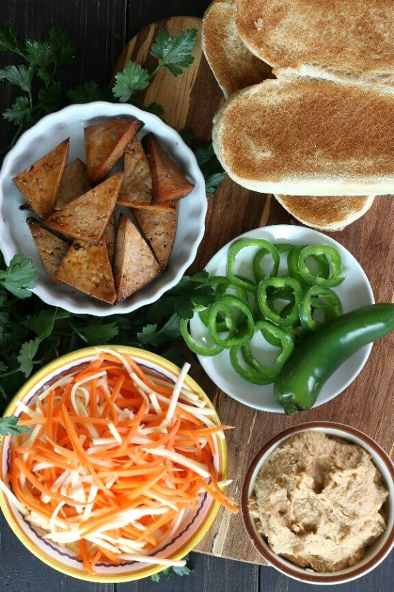 Vegan Banh Mi Sandwich is photographed as Overhead photo of open French Roll opened and toasted and surrounded by bowls of ingredients. Pickled carrots and parsnips, sliced jalapenos and bakes tofu triangles.