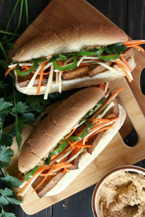 Vegan Banh Mi Sandwich is photographed as Two Long Sub Rolls laying on their back with layers of golden baked tofu with julienned carrots and parsnips and jalepenos.