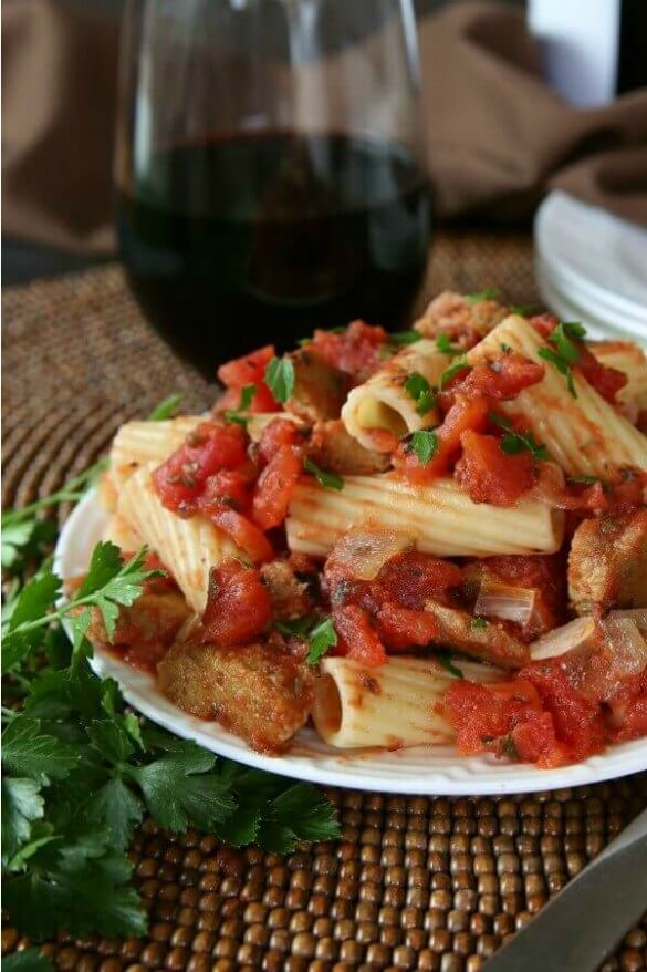 Up Close Photo pf a white plate piled high with fat rigatoni mixed with red marinara sauce and chunky seitan 'sausage'