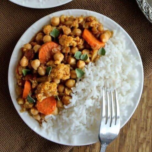 Overhead view divided in half with white rice on one side with rice orange curry colors of mixed veggies.