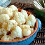 Mildly Marinated Cauliflower in off-center in a blue handled bowl filled with bite sized florets and lightly sprinkled with golden shades of coconut sugar pickling marinade.