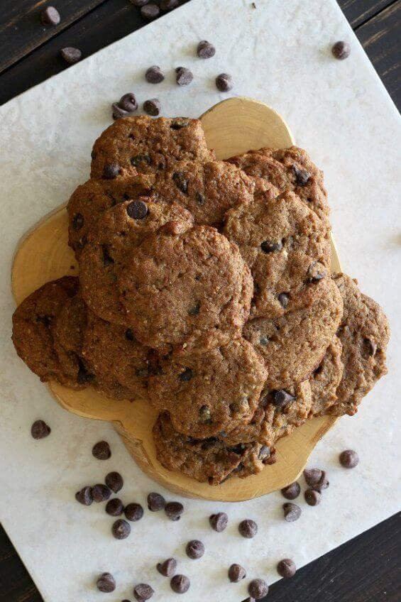 Chocolate Chip Banana Bread Cookies are stacked high on a wooden trivet, granite square and then sprinkled around with chocolate chips.