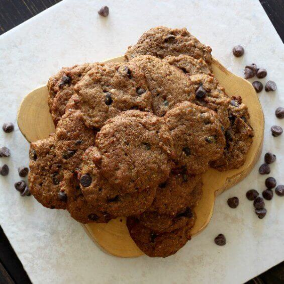Chocolate Chip Banana Bread Cookies are stacked high on a pale wooden trivet with chocolate chips are scattered around.