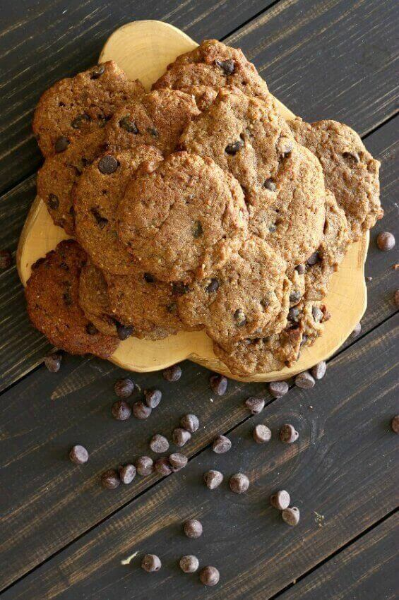 Chocolate Chip Banana Bread Cookies are stacked high on a pale wooden trivet and set against dark wood slats. Chocolate chips are scattered below.