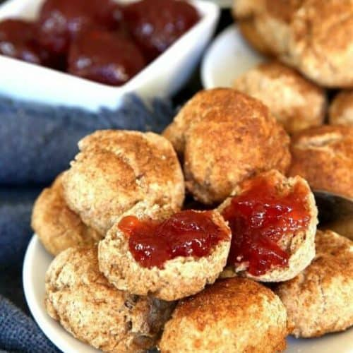 Cinnamon Cookie Biscuits are little fat biscuits with a cinnamon sugar flare. Stacked on a white plate with one open and dolloped with strawberry jam.